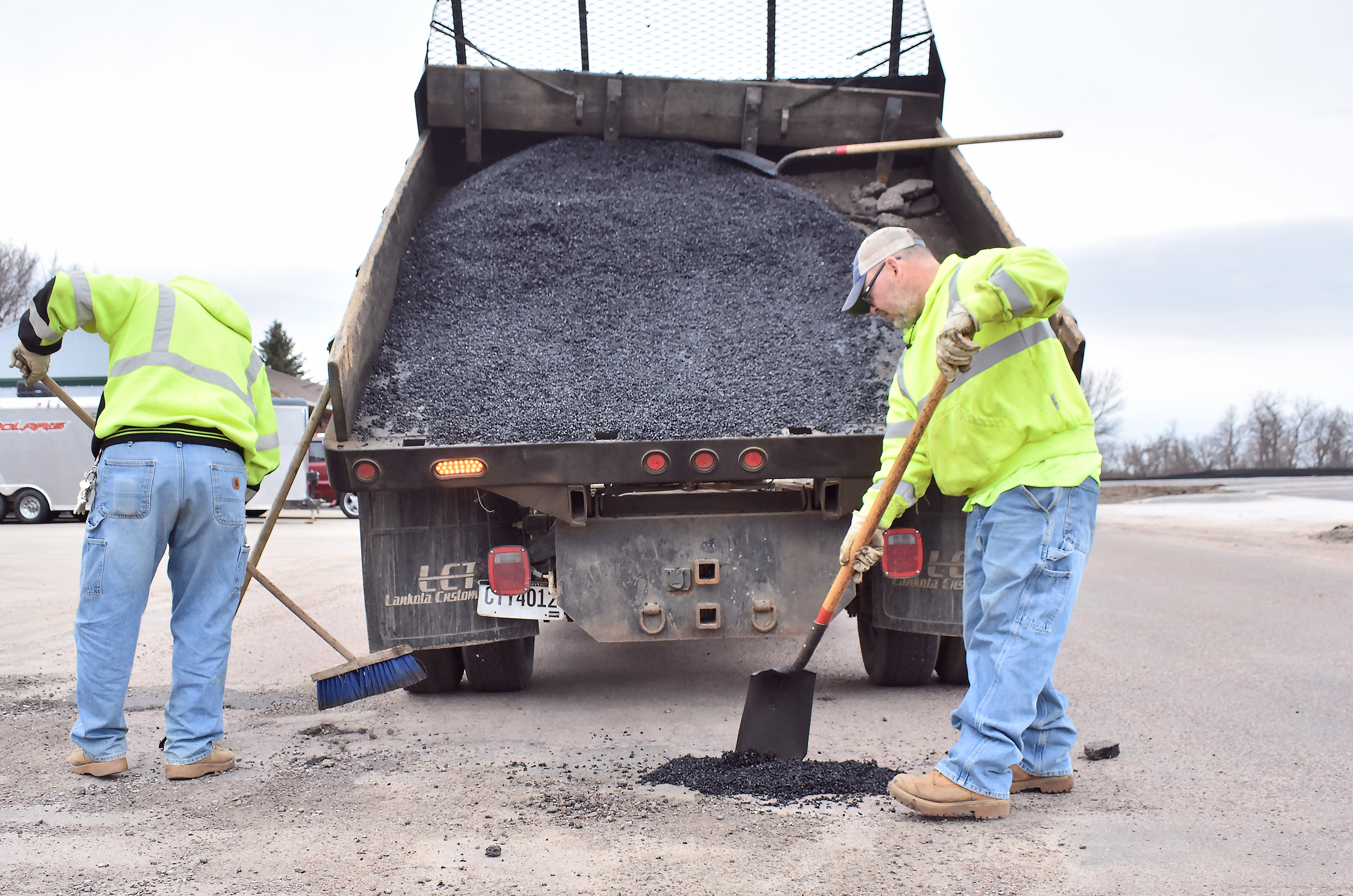 """<span class=""""s1"""">Larry Bixby and Jeramie Olson fill a pothole on Kirkwood Boulevard last week. Potholes plague city streets every spring. The public can now report potholes on the city website link. <strong>Jamie Hult/BV Journal</strong></span>*/"""