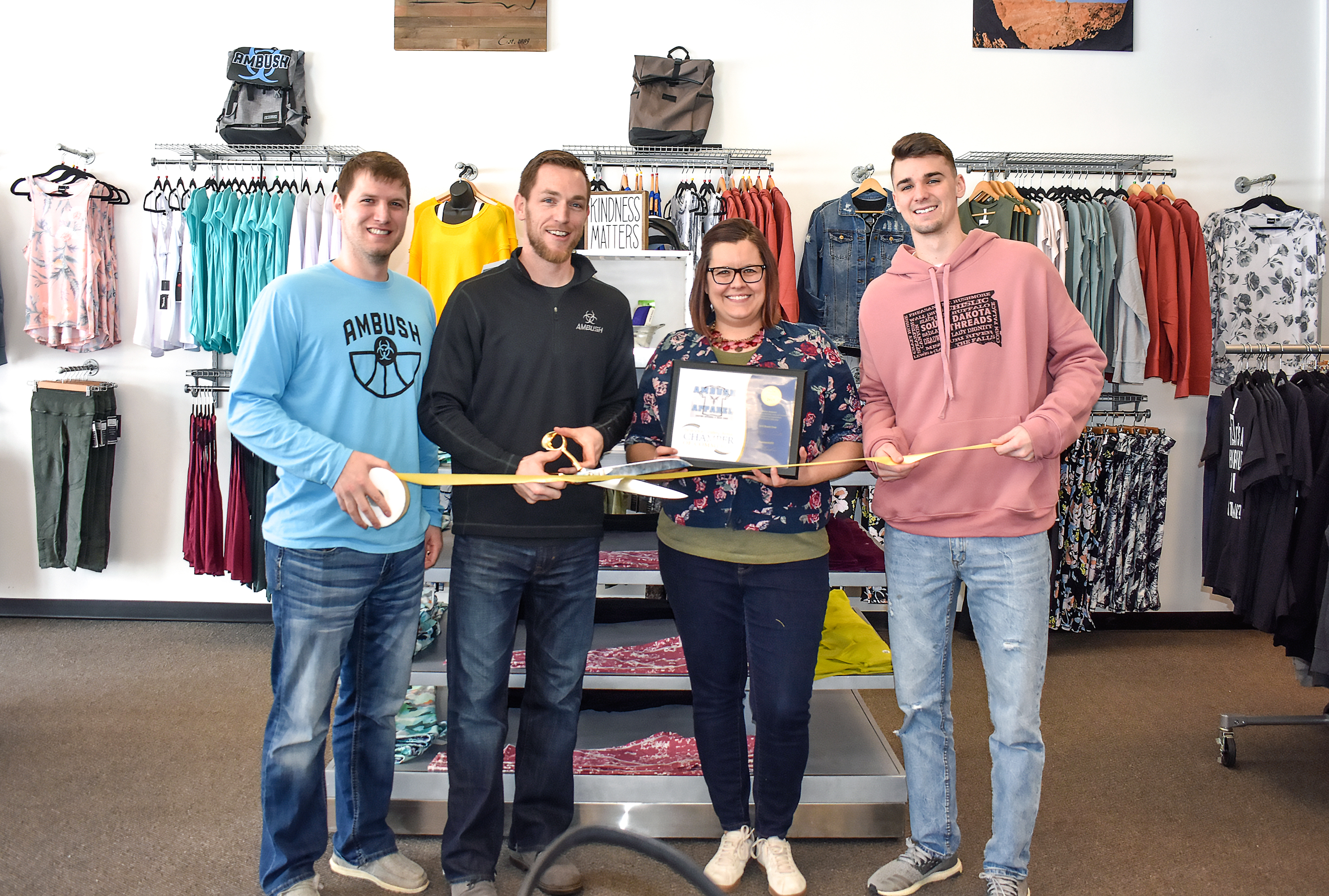 "Staffers at South Dakota Threads, Tri-State Ambush Basketball and Ambush Apparel cut the ribbon Thursday celebrating their membership in the Brandon Valley Area Chamber of Commerce. Owned by Garrett Callahan <i>(second from left)</i>, the screenprinting shop and South Dakota-made boutique opened at 1517 E. Holly Blvd. in 2018. Also pictured are Cory Jacobsen, Jessica Johnson and Trae VandeBerg.<span class=""Apple-converted-space""> <strong>Jamie Hult/BV Journal</strong></span>*/"
