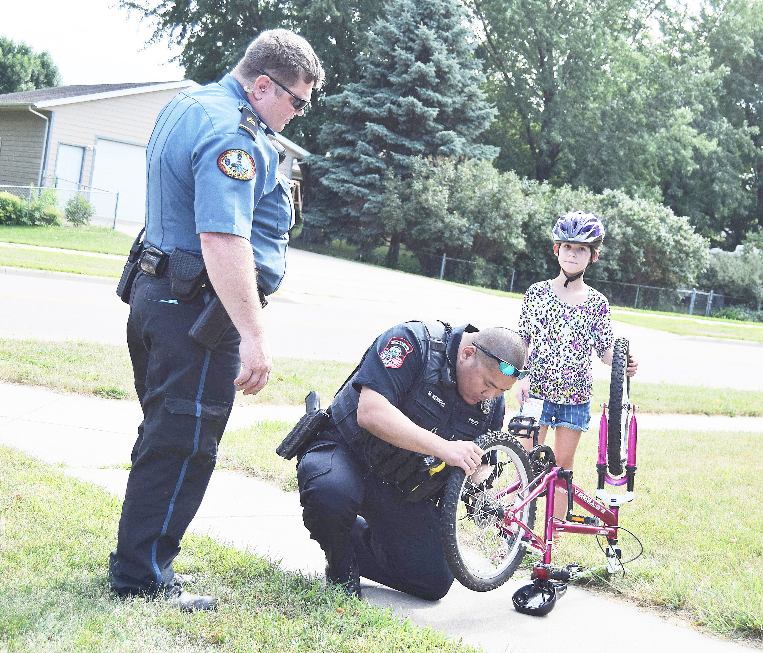 "<span style=""font-size:11px;""><span style=""font-family:arial,helvetica,sans-serif;"">Brandon Police Officer Lee Henning and Sgt. Jason Story with the Minnehaha County Police Reserves came to the rescue of Alexis Wegner, 9, when she had issues with the chain on her bicycle. Along with some assistance in getting her bike into commission, the youngster also scored a free ice cream ticket for wearing her helmet. <strong>Jill Meier/BV Journal</strong></span></span>"