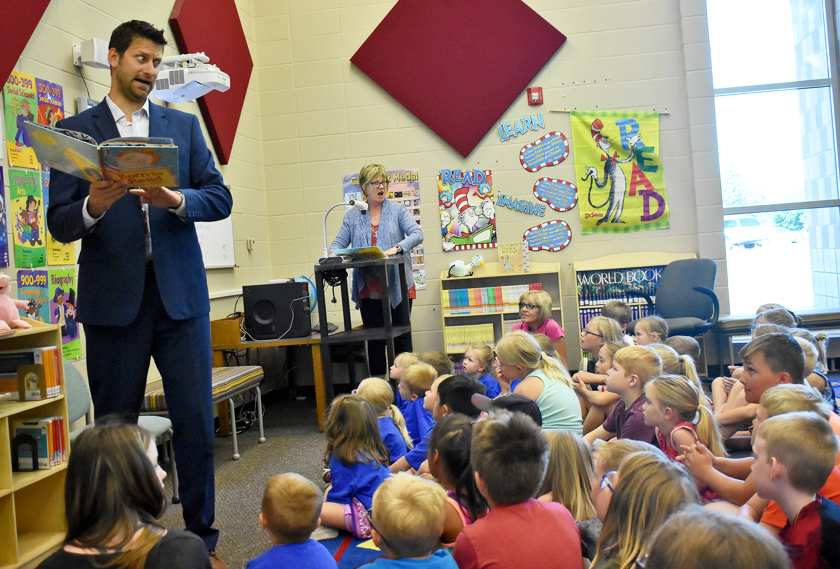 "Brandon Valley superintendent Dr. Jarod Larson delivers an animated page-through of <i>Born to Read</i> by Judy Sierra on June 6, kicking off a series of Wednesday story times in conjunction with the summer lunch program at Brandon Elementary.<span class=""Apple-converted-space""> </span>Story times will be 10:30 a.m. and 11:30 a.m. Wednesdays in the Brandon Elementary library. Kids 18 years old and under eat free from 11 a.m. to 12:30 p.m. weekdays through July 27, and lunch is $4 for adults. <strong>Jamie Hult/BV Journal</strong>*/"