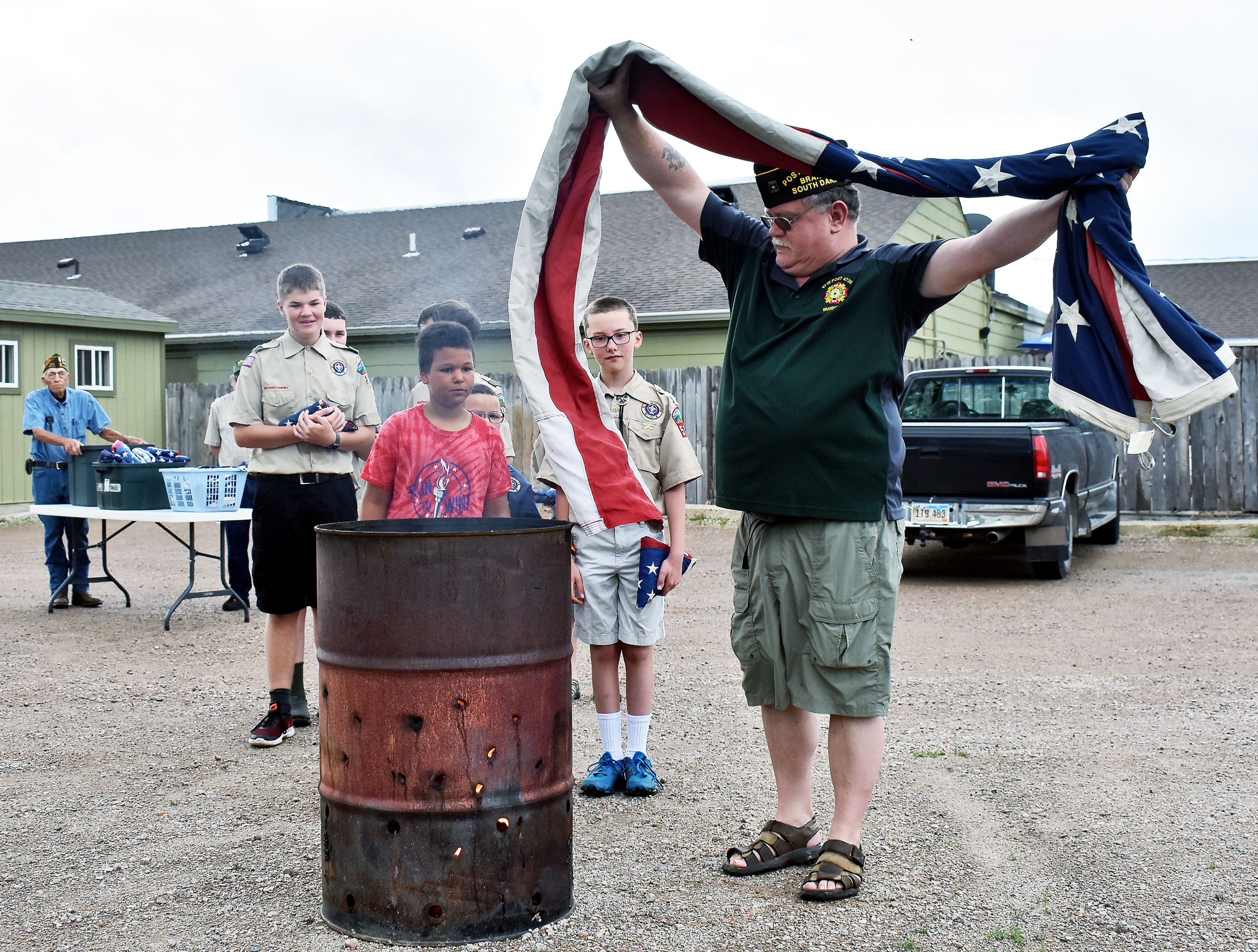 "Brandon VFW Post Commander Troy Zimmerman demonstrates proper flag disposal Saturday to members of Boy Scout Troop 212 and Cub Scout Pack 582 <i>(from left) </i>Brayden Greene, Isaiah Gunnick and Noah Reyelts.<span class=""Apple-converted-space""> <strong>Jamie Hult/BV Journal</strong></span>*/"