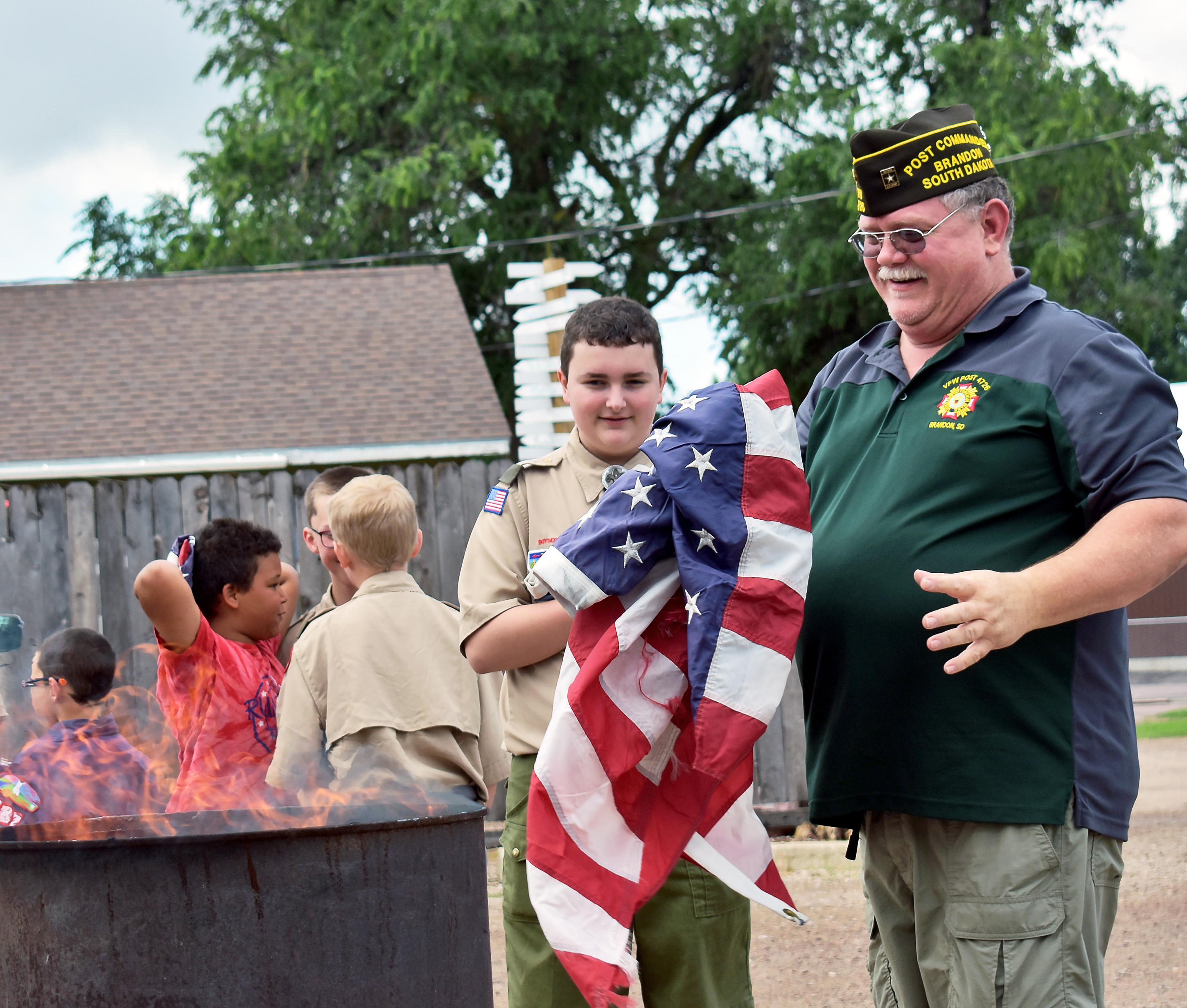 Brady Simons <i>(above</i>) and Isak Gunnick <i>(below) </i>hand flags to Troy Zimmerman at the VFW's annual retirement ceremony June 9.*/