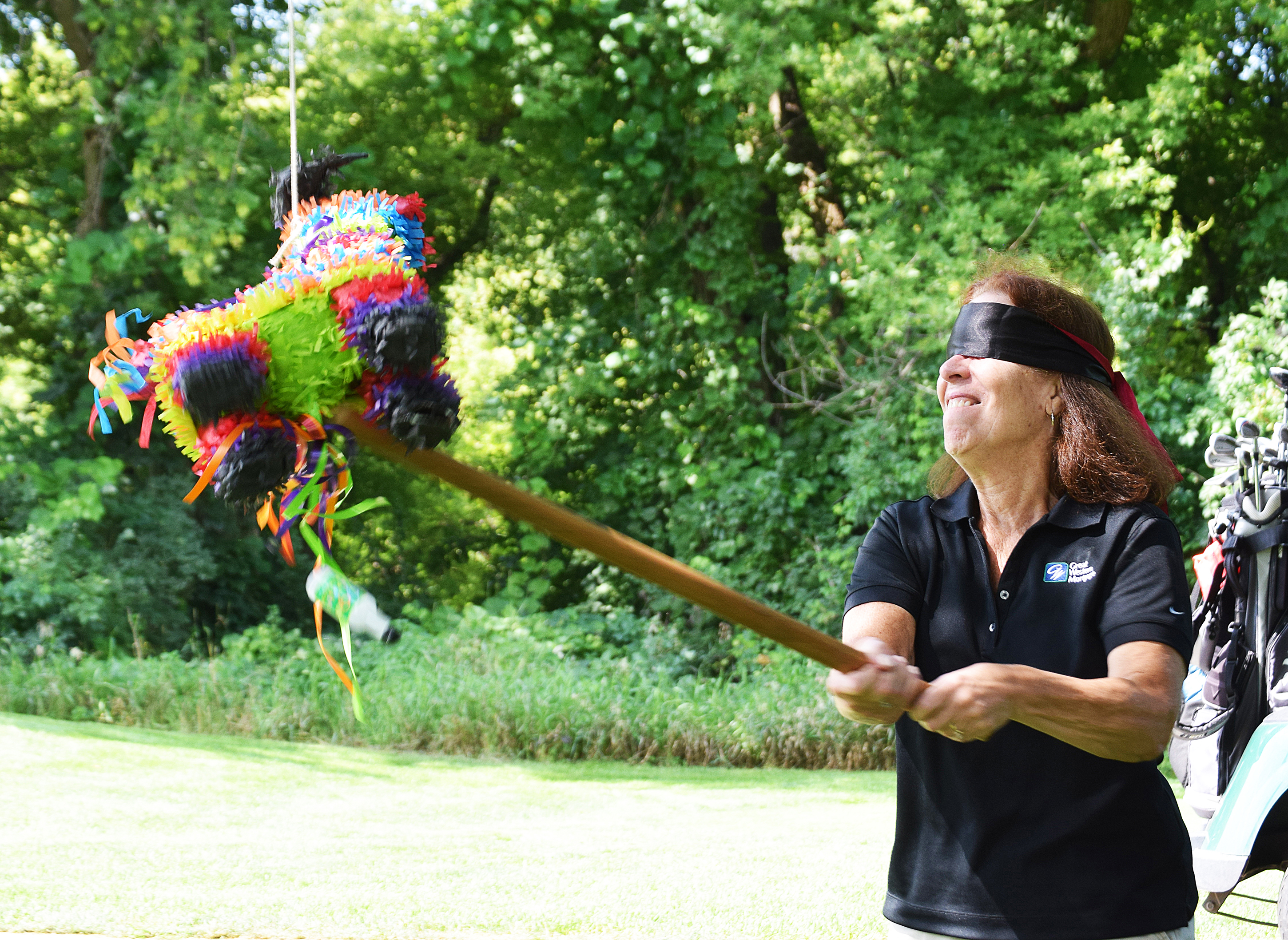 "Brandon Valley Chamber of Commerce took their annual golf tournament ""south of the border"" this year, giving the Aug. 2 event a Mexican fiesta theme. Cheryl Erickson of Great Western Bank takes a whack at the pinata, which was one of a variety of fun games the approximate 120 golfers took part in on the links of the Brandon Municipal Golf Course.<span class=""Apple-converted-space""> <strong>Jill Meier/BV Journal</strong></span>*/"