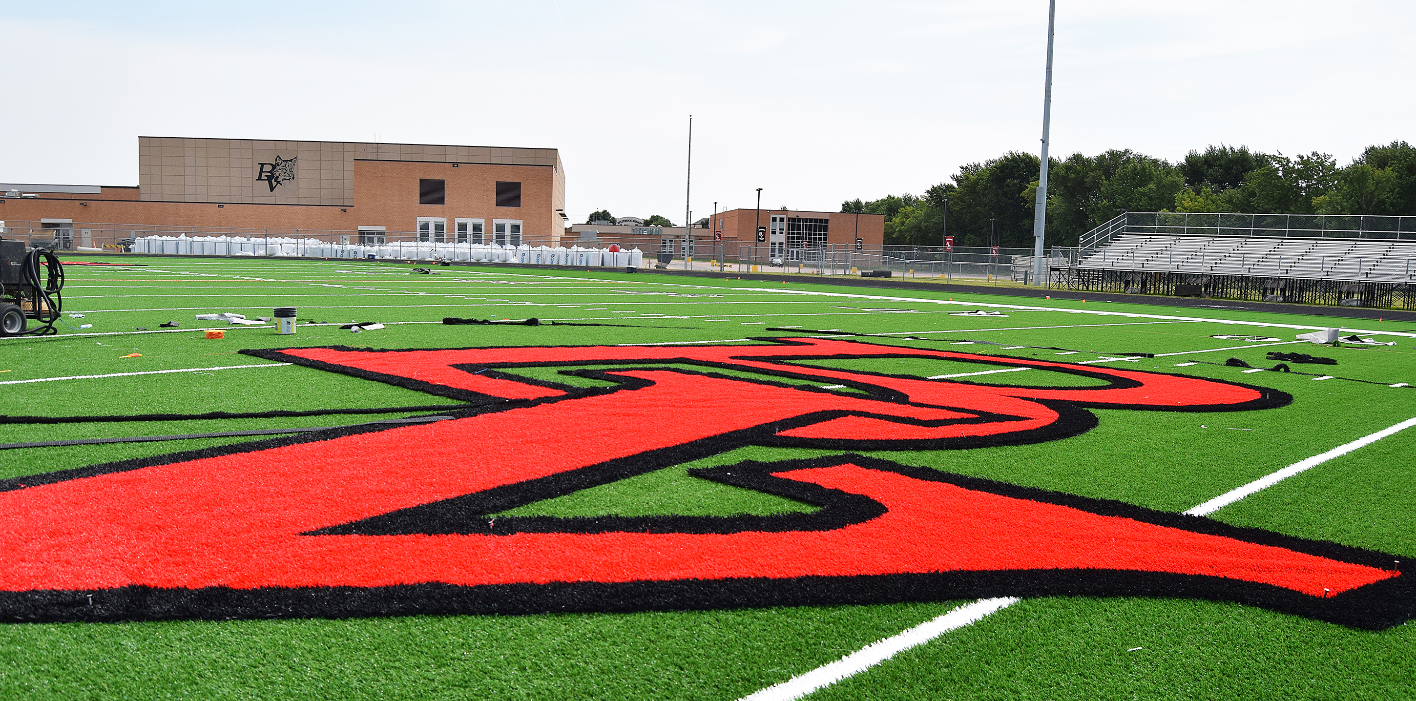 "The finishing touches on the artificial turf at the Brandon Valley Stadium got underway last week. Workers began piecing in the midfield ""BV"" art, sideline yard numbers and ""LYNX"" in each endzone. The first event scheduled on the new turf is the Aug. 21 Lady Lynx-West Central soccer game.<span class=""Apple-converted-space""> <strong>Jill Meier/BV Journal</strong></span>*/"